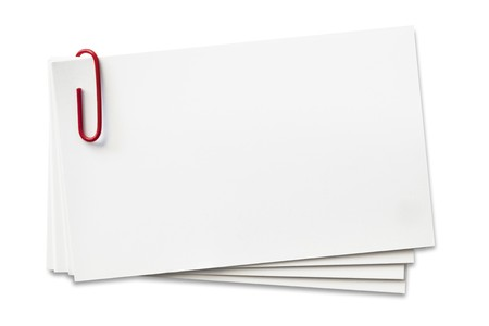 paperclip: Stack of business cards with red paperclip.