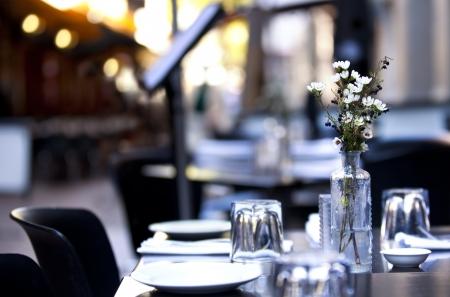 瀬戸物: カジュアルな雰囲気を持つの舗装カフェ テーブル。被写体の背景を持つ花に焦点を当てます。 写真素材