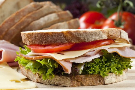 crusty: Sandwich with Swiss cheese, ham, tomato and curly lettuce, on crusty fresh-sliced bread. Stock Photo