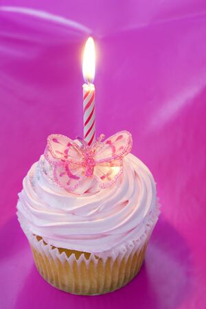 Cupcake with pink frosting, a butterfly and a candle, over vibrant background. photo