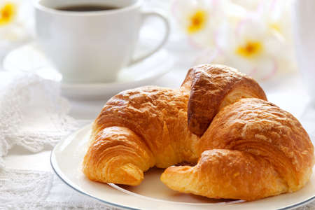 Croissant with coffee, on sunlit breakfast table with lace napkins. photo