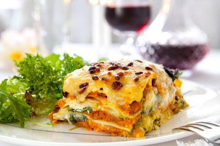 redwine: Vegetarian lasagne topped with toasted pine nuts and melting cheeses.  With salad and red wine. Stock Photo