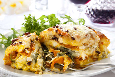 pine nuts: Vegetarian lasagne topped with toasted pine nuts and melting cheeses.  With salad and red wine. Stock Photo