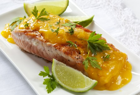 cooked fish: Atlantic salmon, grilled and served with a buttery orange sauce and lime wedges.