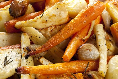 parsnips: Roasted root vegetables, in close up.  Includes carrots and parsnips, plus potatoes, butternut squash, shallots and garlic bulbs.