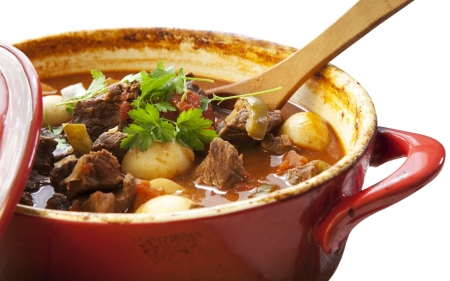 Goulash: Beef stew in a red crock pot, ready to serve.