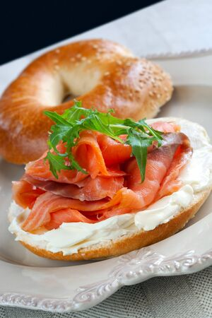 bagel: Bagel with smoked salmon and cream cheese, garnished with arugula. Stock Photo