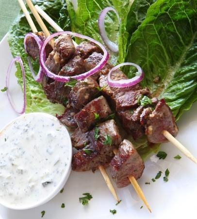 meat skewers: Lamb kebabs with tzatziki cucumber yogurt.  On kos lettuce, with red onions.