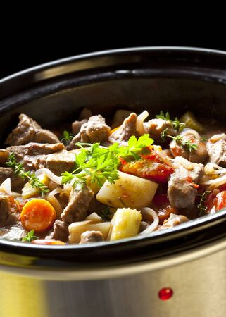 cooker: Beef stew cooking in a clow cooker.  Hearty warming winter food.
