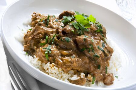 beef stew: Beef stroganoff over white rice, garnished with parsley. Stock Photo