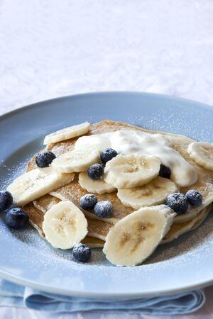 powdered sugar: Banana and blueberry pancakes, topped with yogurt and powdered sugar.