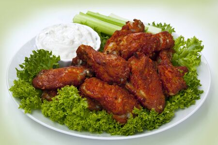 hot wings: Platter of buffalo wings with a blue cheese dipping sauce and celery sticks.  Hot and spicy!