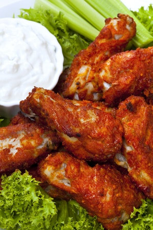 Platter of buffalo wings with a blue cheese dipping sauce and celery sticks.  Hot and spicy! photo