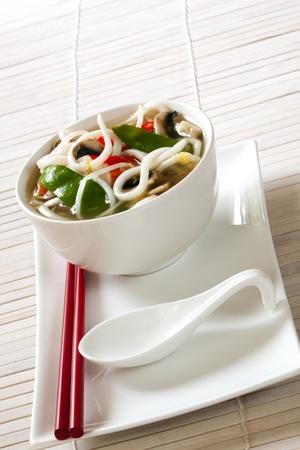 soup spoon: Scodella di zuppa di noodle giapponesi udon, con un cucchiaio di minestra e le bacchette di rosse.