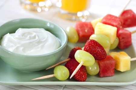 Platter of fruit skewers with a dish of yogurt.  Healthy party food, with orange juice behind. photo
