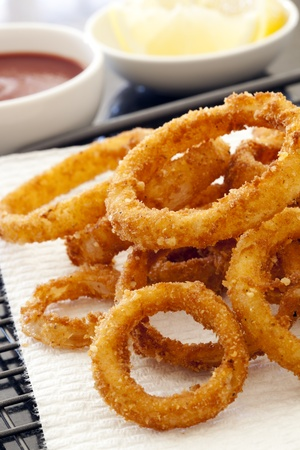 Fried onion rings on absorbent paper, with ketchup and lemon. Stock Photo - 9273000