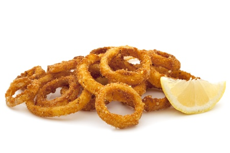 lemon wedge: Pile of fried onion rings with a lemon wedge, over white background.