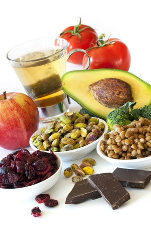 Foods rich in antioxidants, over white background.  Includes cranberries, apple, green tea, tomatoes, broccoli, avocado, lentils, pistachios and dark chocolate. photo