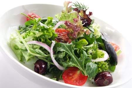 Bowl of salad, with curly lettuce, arugula, cherry tomatoes, black olives and red onion. Stock Photo - 9412561