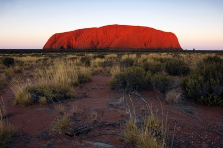 Monolith: Uluru, Australia - May 11, 2008:  Uluru or Ayers Rock, Central Australia, at sunset.  This icon is the largest monolith in the world, and glows a stunning red at sunset and sunrise.  It is sacred to its Aboriginal owners. Editorial