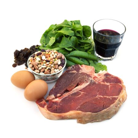 iron: Food sources of iron, including red meat, eggs, spinach, peas, beans, raisins and prune juice.  Isolated on white.