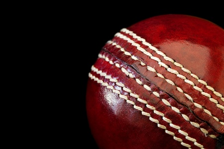 cricket field: Cricket ball in close-up, over black background.  Shallow depth of field.