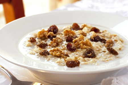 raisin: Bowl of oatmeal topped with raisins, walnuts and brown sugar.  Healthy eating.