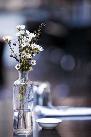 Flowers in glass bottle, on table at casual pavement cafe.  Shallow depth of field. photo