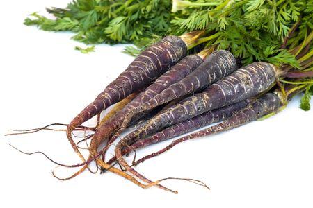 heirloom: Bunch of heirloom purple carrots, over white background.  High in antioxidants.