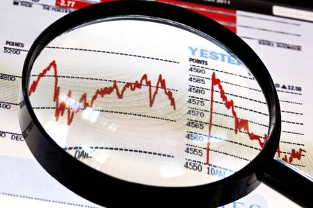 Magnifier over screen of digital tablet, showing financial graphs. photo
