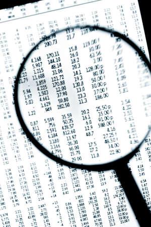 stockmarket: Magnifier over screen of digital tablet, showing financial figures.
