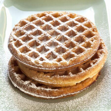 powdered sugar: Stack of waffles with powdered sugar.
