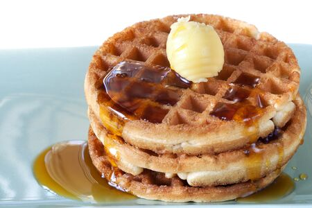 belgian: Stack of waffles with maple syrup and butter.