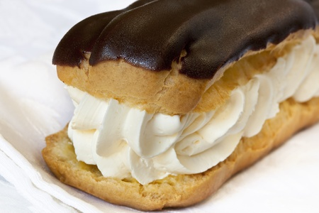 eclair: Chocolate eclair filled with fresh cream.  Close-up view. Stock Photo