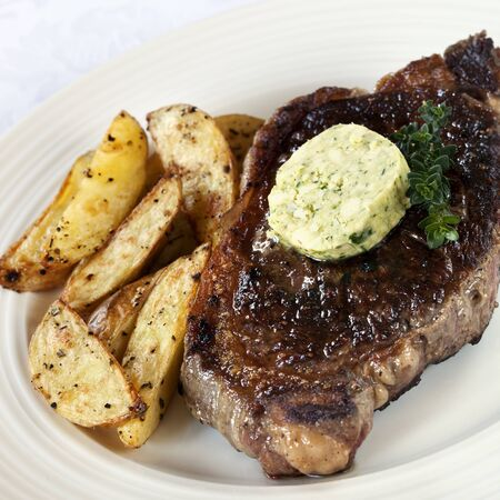 wedges: Steak with herbed butter and potato wedges, garnished with thyme.  Not so healthy, but delicious! Stock Photo