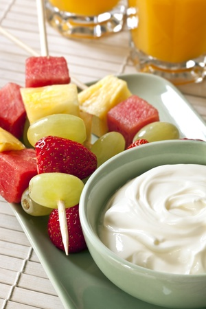Sticks of fresh fruit with a bowl of yogurt and orange juice.  Healthy snacking. photo