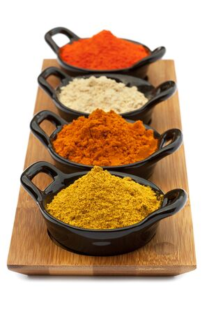 Tray of spices in small black bowls.  Includes Madras curry powder, Malaysian curry powder, ground ginger, and saffron. Stock Photo - 9887650