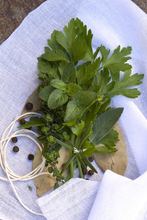 Bouquet garni of fresh herbs and peppercorns, on muslin ready for tying. Stock Photo