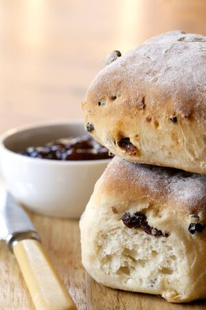 scone: Fruit scones, with bowl of strawberry jam.  Shallow depth of field.