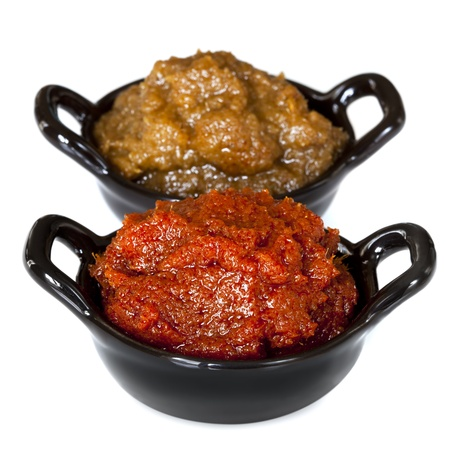 curry powder: Red and green curry paste, in small black bowls, isolated on white.