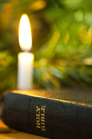 bible christmas: Old Bible with Christmas candle.  Focus on words Holy Bible. Stock Photo