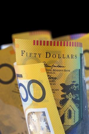 australian dollar notes: Australian fifty dollar notes, over black background.