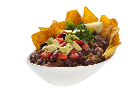 ground beef: Chili Con Carne, topped with cornships, avocado and tomato.  Isolated on white.