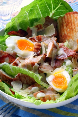 Chicken Caesar salad with eggs, bacon, croutons, kos, and shaved parmesan. photo