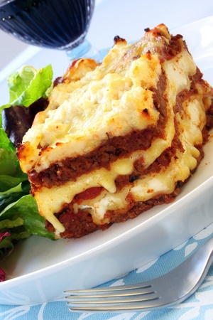 melting: Beef lasagne with salad and red wine.  Delicious melting mozzarella and ricotta cheeses. Stock Photo