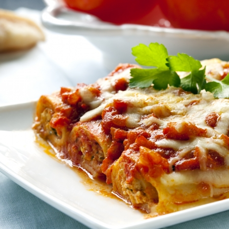 Cannelloni topped with melting cheeses, ready to enjoy. photo