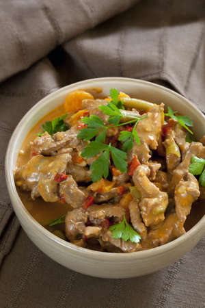 beef curry: Bowl of red Thai beef curry, over brown linen.
