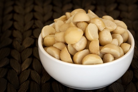 macadamia nut: Bowl of macadamia nuts, over wicker background. Stock Photo