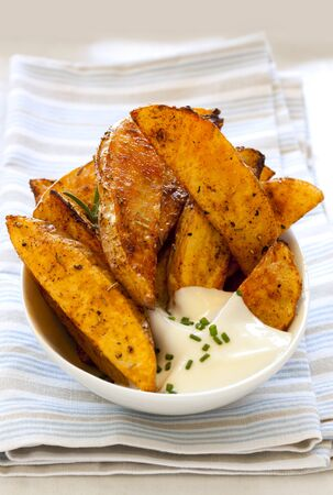 wedges: Spicy potato wedges in small bowl with sour cream.