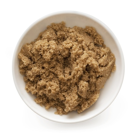 Bowl of brown sugar, isolated on white.  Overhead view. photo
